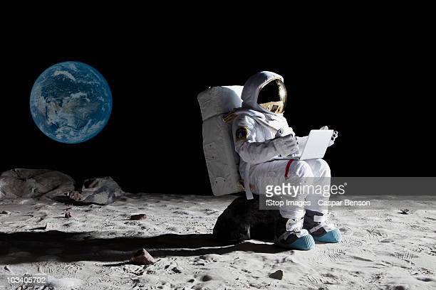 an astronaut on the moon sitting on a rock using a laptop - astronaut stock-fotos und bilder