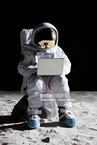 An astronaut on the moon sitting on a rock using a laptop