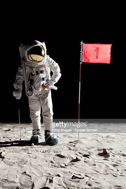 an astronaut on the moon standing next to number 1 hole flag - golf humour photos et images de collection