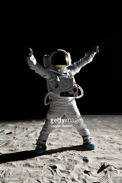 An astronaut on the moon with his arms raised in victory