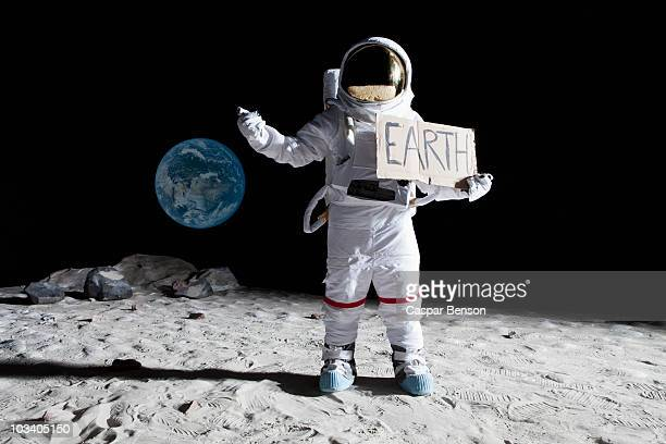 An astronaut on the moon with his thumb out, holding 'EARTH' sign