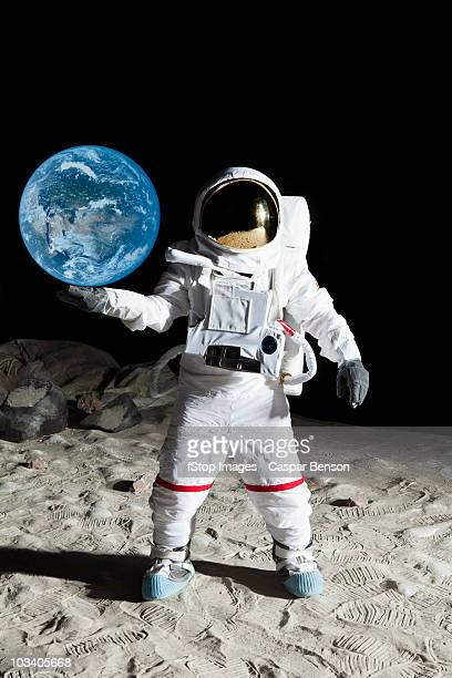 An astronaut on the moon's surface pretending to hold the earth