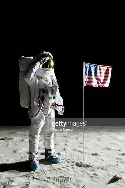 An astronaut on the surface of the moon saluting an American flag