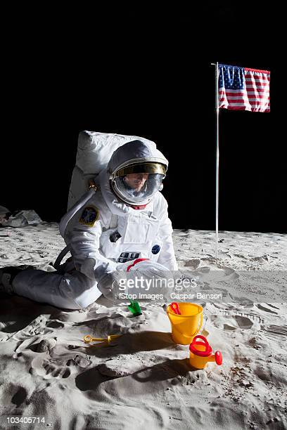 An astronaut playing with a sand pail and shovel on the moon