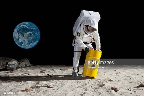 An astronaut rolling a drum of toxic material on the moon surface