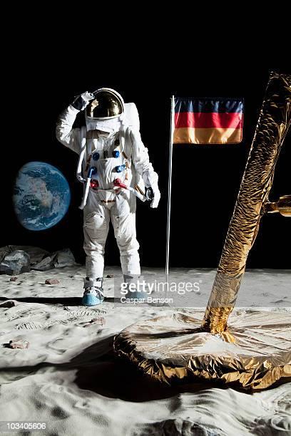 An astronaut standing near a lunar lander salutes an German flag