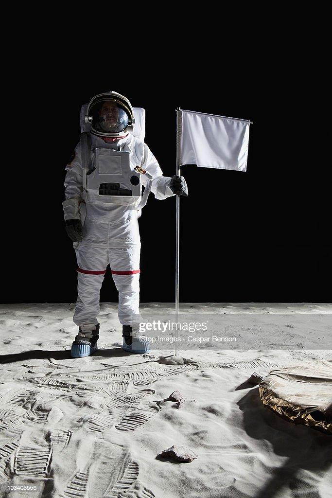 An astronaut standing next to a white flag : Stock Photo