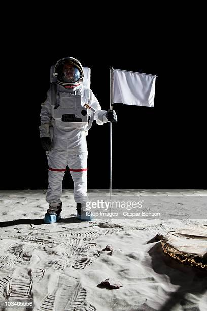 an astronaut standing next to a white flag - flag stock pictures, royalty-free photos & images