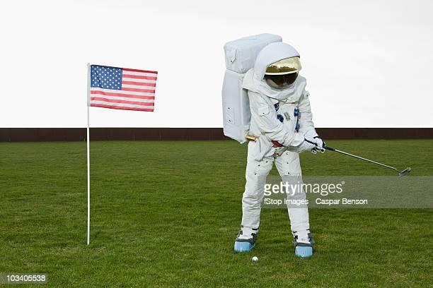 an astronaut swinging a golf club next to an american flag - golf lustig stock-fotos und bilder