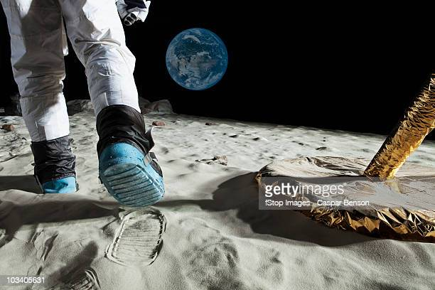 an astronaut walking on the moon, rear view, low section - astronauta fotografías e imágenes de stock