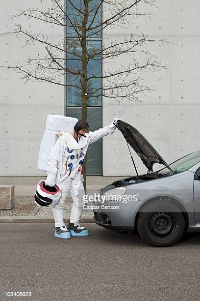 An astronaut with car troubles