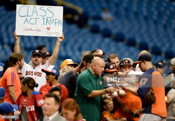 An Astros fan thanks Tampa as Chris Devenski of the Houston Astros signs autographs before their game versus the Texas Rangers at Tropicana Field on...