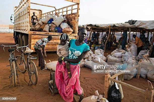 An asylum seeker and her baby from Sudan who recently arrived in South Sudan stands beside a truck holding some of her belongings before she is...
