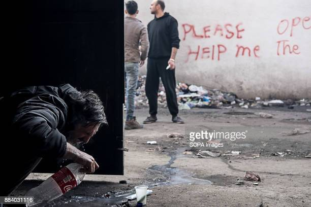 THE BARRACKS BELGRADE SERBIA An asylum seeker chokes on water as he brushes his teeth at the door of an abandoned building Thousands of refugees...