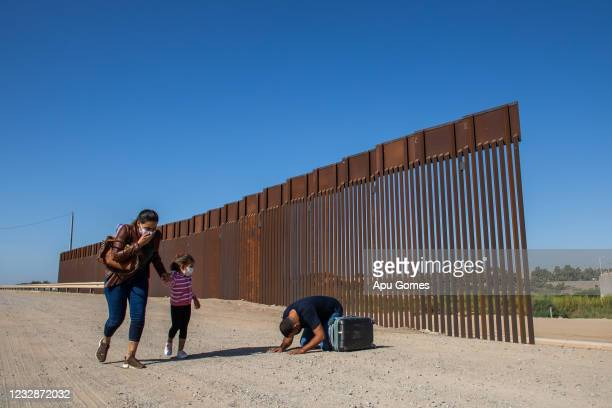 An asylum seeker from Cuba kneels as he and his family prepare to turn themselves in to the US Border Patrol on May 13, 2021 in Yuma, Arizona. The...