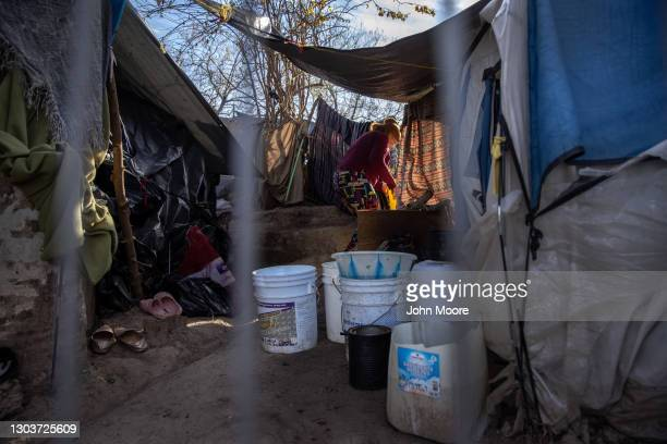 An asylum seeker goes to collect fresh water distributed at a migrant camp at the U.S.-Mexico border on February 23, 2021 in Matamoros, Mexico. U.S....
