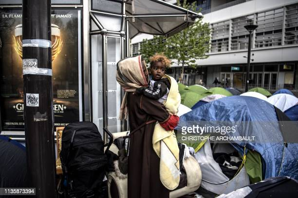 TOPSHOT An asylum seeker holds her oneyearold son as they stand outside their a tent at a makeshift camp housing mainly families at Porte...