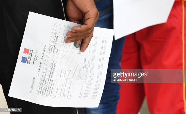 An asylum seeker rescued by the Aquarius rescue ship and another ship in the Mediterranean sea holds an official document delivered by the French...