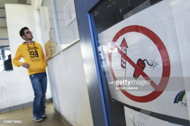 An asylum seeker stands next to a sign in Arabic script pointing out that no pyrotechnic items may be ignited within the state reception facility at...