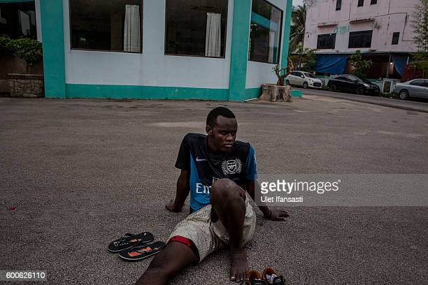 An asylum seeker takes a rest after playing football in front of the Kolekta hotel where hundreds of refugees and asylum seekers stay for years while...