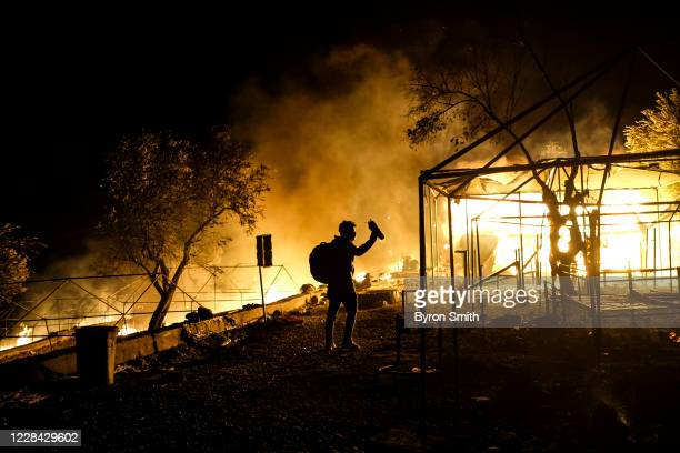 An asylum-seeker retrieves his belongings from his burnt down tent as fires continue to rage for a second night in the Moria migrant camp on...