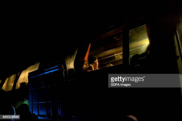 An asylumseekers waits aboard a bus that will transfer him and other migrants to a camp where they are required to register with authorities after in...