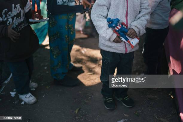 An asylumseeking child holds a Marvel Comics' Captain America action figure at a makeshift camp near the US and Mexican border crossing in Tijuana...