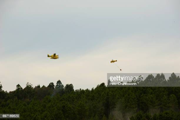 JOãO COJA ARGANIL PORTUGAL An AT802F FIRE BOSS Air Tractor firefighting aircraft and a Russian made Kamov KA32 firefighting helicopter drop water on...