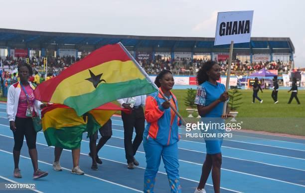An athlet holds the Ghanaian flag as they march during the opening of the 21st African Senior Athletics Championships at the Stephen Keshi Stadium in...