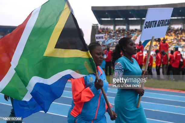 An athlet holds the South African flag as they march during the opening of the 21st African Senior Athletics Championships at the Stephen Keshi...