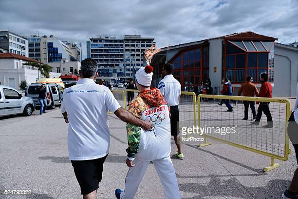 An athlete carries the Olympic Flame from the port of Thessaloniki to the next stop The Olympic Flame of the SOCHI 2014 winter olympics arrived today...