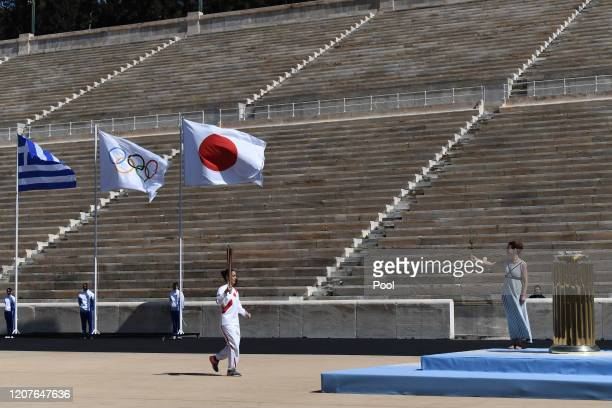An Athlete carries the Olympic torch during the Flame Handover Ceremony for the Tokyo 2020 Summer Olympics on March 19, 2020 in Athens, Greece. The...