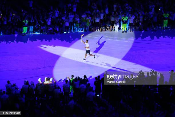 An athlete carries the torch games during the opening ceremony of the 2019 Universiade in Naples inside the San Paolo stadium