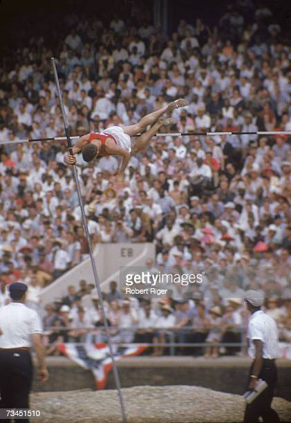 An athlete competes in the pole vault competition at the AAU men's championship as the audience and officials look on Los Altos California July 1959