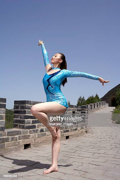 an athlete doing gymnastics on the great wall of china. - gymnastics poses stock pictures, royalty-free photos & images