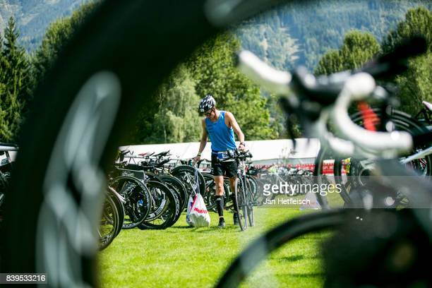 An athlete drops off his bike at the transition area ahead of tomorrow's IRONMAN 703 Zell am SeeKaprun triathlon event on August July 26 2017 in Zell...