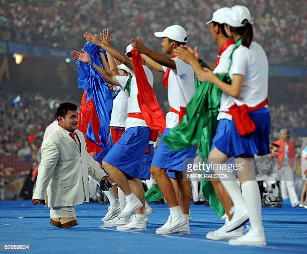 An athlete from Mexico walks past cheerleaders as they parade at the National Stadium during the opening ceremony for the 2008 Beijing Paralympic...