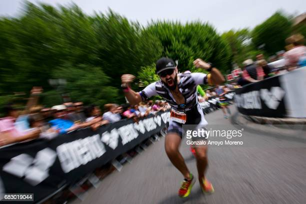 An athlete gestures to the camera as he competes during the running course of the Ironman 703 Pays d'Aix on May 14 2017 in AixenProvence France