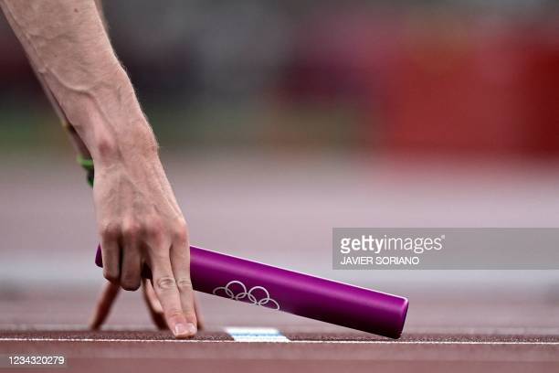 An athlete holds a relay baton ahead of the mixed 4x400m relay heats during the Tokyo 2020 Olympic Games at the Olympic Stadium in Tokyo on July 30,...