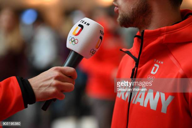 An athlete is being interviewed with a microphone that has Team D and the Olympic Rings printed on it at the 2018 PyeongChang Olympic Games German...
