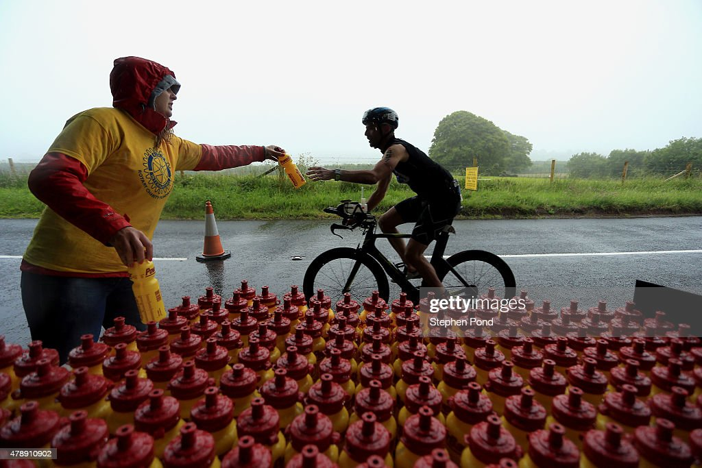 An athlete is handed water as he passes a food station during the Ironman 70.3 Exmoor event on June 28, 2015 in Exmoor National Park, England.