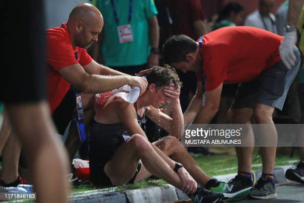TOPSHOT An athlete is helped to cool down after competing in the Men's 50km Race Walk final at the 2019 IAAF World Athletics Championships in Doha on...