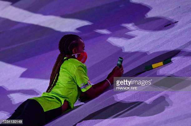 An athlete lies on the ground and looks at her phone as delegations enter the Olympic Stadium during the opening ceremony of the Tokyo 2020 Olympic...