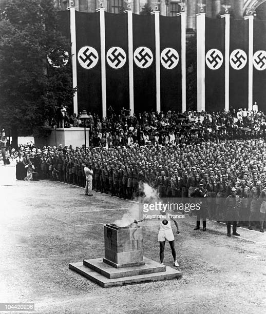 An Athlete Lighting The Olympic Torch In Berlin'S Lustgarten Upon The Opening Ceremony Of The Xith Olympic Games In August 1936