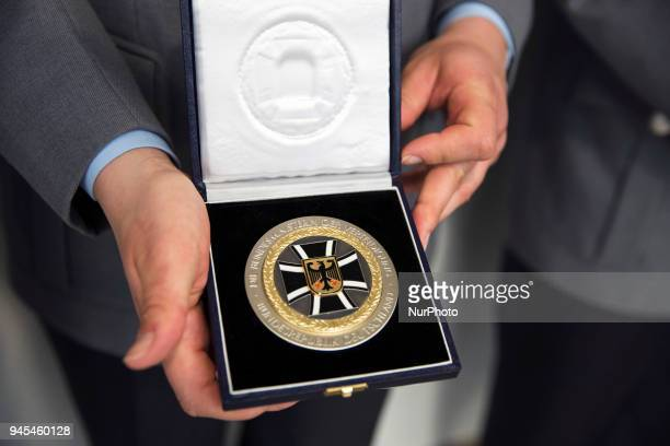 An athlete member of the German Army holds a medal during a ceremony to honour the members of the Bundeswehr who attended the Winter Olympic Games in...