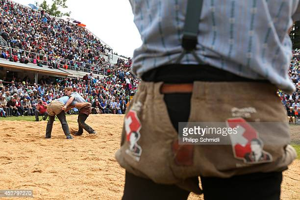 An athlete observes a fight during the Alpine Wrestling Festival BruenigSchwinget at the top of the Bruenig Pass on July 27 2014 in Meiringen...