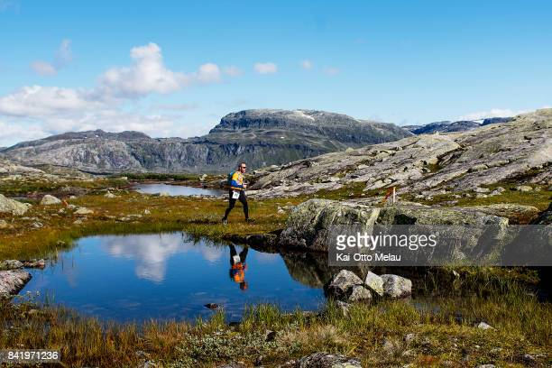 An Athlete passing one of the many lakes at Hardangervidda Marathon on September 2 2017 in Eidfjord Norway Hardangervidda Marathon goes through parts...