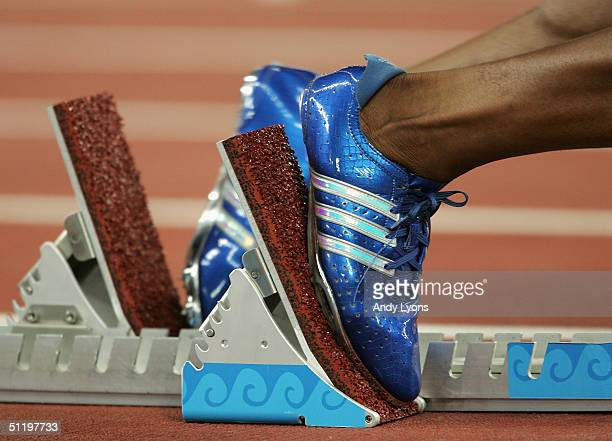 An athlete places his feet in the starting block during the men's 400 metre event on August 20 2004 during the Athens 2004 Summer Olympic Games at...