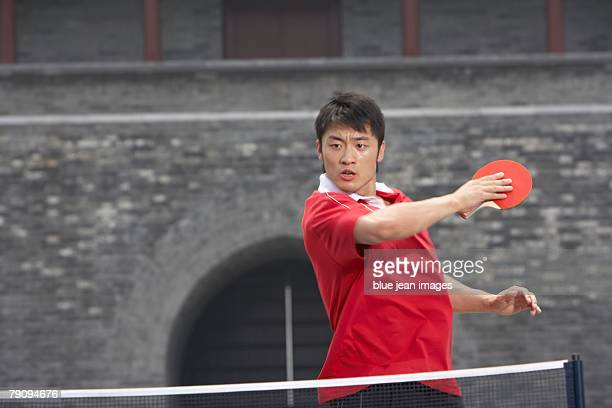 An athlete playing table tennis in front of an ancient Chinese building.