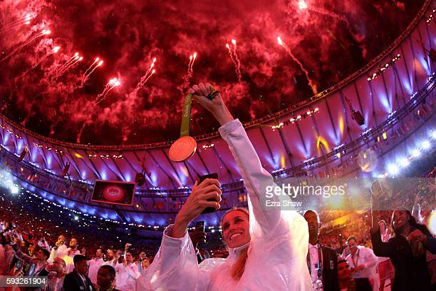 An athlete takes a photo of their medal as fireworks explode near the conclusion of the Closing Ceremony on Day 16 of the Rio 2016 Olympic Games at...